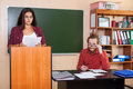 Young Girl Student Prepare Report Seminar Standing At Platform In Classroom, Professor Listen High Royalty Free Stock Photo