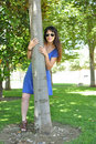 Young girl  with sunglasses hugging a tree Stock Image