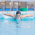 Young girl swimming butterfly stroke style in goggles and cap in the blue water pool Stock Photography
