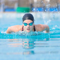 Young girl swimming butterfly stroke style in goggles and cap in the blue water pool Stock Images