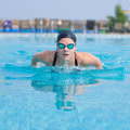 Young girl swimming butterfly stroke style in goggles and cap in the blue water pool Royalty Free Stock Photos