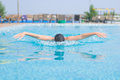 Young girl swimming butterfly stroke style in goggles and cap in the blue water pool Royalty Free Stock Images