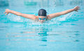 Young girl swimming butterfly stroke style in goggles and cap in the blue water pool Stock Image