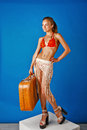 Young girl in swimsuit holding a suitcase. Royalty Free Stock Photo