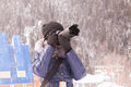 Young girl takes pictures winter mountain landscape in a snow storm on a SLR camera with telephoto lens Royalty Free Stock Photo