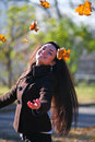 Young girl throwing autumn leaves Stock Images