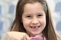 Young girl without a tooth while brushing teeth little in the bathroom Stock Photo