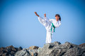 Young girl training karate against the sky Stock Photo