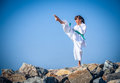 Young girl training karate against the sky Royalty Free Stock Photos