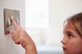 Young girl turning off light switch close up of Royalty Free Stock Photo