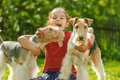 Young girl and two fox terriers little with dogs of breed terrier on green lawn Royalty Free Stock Images