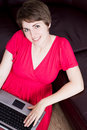 Young girl using a laptop on brown sofa Royalty Free Stock Photography