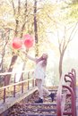 Young girl walking in the autumn park with heart shaped balloons Stock Photos