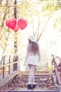 Young girl walking in the autumn park with heart shaped balloons Stock Photo