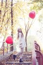 Young girl walking in the autumn park with heart shaped balloons Royalty Free Stock Photography