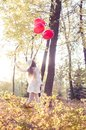 Young girl walking in the autumn park with heart shaped balloons Stock Photography