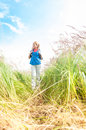 Young girl walking in meadow with backpack on. Stock Image