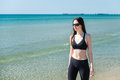 A young girl walks along the beach after a run in sunglasses Royalty Free Stock Photo