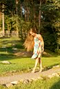 young girl walks the park barefoot in the bright sun in a summer sarafan
