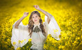 Young girl wearing elegant white blouse posing in canola field outdoor shot portrait of beautiful long hair brunette with large Stock Photography