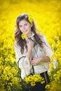 Young girl wearing elegant white blouse posing in canola field, outdoor shot. Portrait of beautiful long hair brunette
