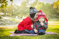 Young girl whispers a secret to baby brother little her wearing winter coats and hats sitting outdoors at the park Royalty Free Stock Images