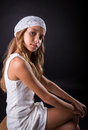 Young girl with white cap and sober look sitting on black backgr long hair a a background Stock Photo