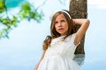 Young girl in white dress resting against tree. Royalty Free Stock Photo