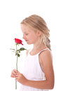 Young girl in white dress smelling a red rose against background Royalty Free Stock Images