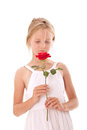 Young girl in white dress smelling a rose red against background Royalty Free Stock Photos