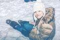 Young girl in white hat sitting in snow Royalty Free Stock Photo