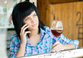 The young girl with a wine glass of speaks by phone Royalty Free Stock Image
