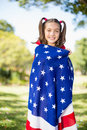 Young girl wrapped in American flag Royalty Free Stock Photo