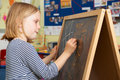 Young Girl Writing On Blackboard In School Classroom Royalty Free Stock Photo