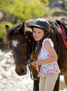 Young girl 7 or 8 years old holding bridle of little pony horse smiling happy wearing safety jockey helmet in summer holiday Royalty Free Stock Photo