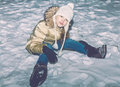 Young girl in yellow jacket sitting in snow Royalty Free Stock Photo