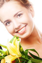Young girl with yellow lily laughs Royalty Free Stock Photo