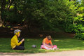 Young girl and young boy in sportswear and sports helmets sit re resting talking the park Royalty Free Stock Photo