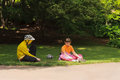Young girl and young boy in sportswear and sports helmets sit resting talking the park Stock Photos