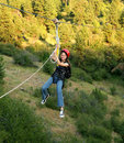 Young girl on a zip line over canyon. Royalty Free Stock Images