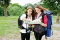Young girls with backpacks two view map Royalty Free Stock Photography