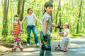 Young girls and boy in protective equipment and rollers scating Royalty Free Stock Photo