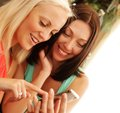 Young girls checking out their new mobilephone cute at home indoor Stock Photos