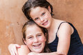 Young girls cousins portrait hugs friends and after a summer swim close up head shoulders photo against brown plastered wall Stock Photography