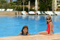 Young girls at edge of pool two pretty in swimming costumes the a large blue where there are unoccupied loungers Royalty Free Stock Photos