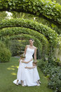 Young girls embracing bride under ivy arches full length of Stock Image