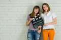 Young girls holding a clapboard two smiling attractive Stock Photography