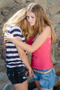 Young girls hug teenage girl comforting crying friend with warm Stock Photos