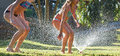 Young girls playing jumping in a garden water lawn sprinkler Royalty Free Stock Photo