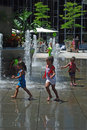 Young girls playing in urban fountain to beat heat Royalty Free Stock Photo